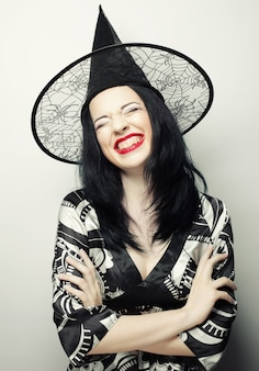 Strega divertente. giovane donna felice con il cappello canival. studio girato.