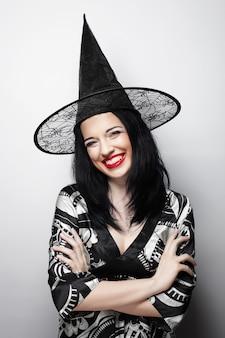 Strega divertente. giovane donna felice con cappello canival. colpo dello studio.