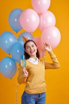 Donna divertente in berretto che tiene un bicchiere di bevanda, sfondo giallo. la bella persona femminile ha ricevuto una sorpresa, un evento o una festa di compleanno, una decorazione di palloncini
