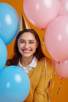 Donna divertente in berretto. la bella persona femminile ha ricevuto una sorpresa, un evento o una festa di compleanno, palloncini