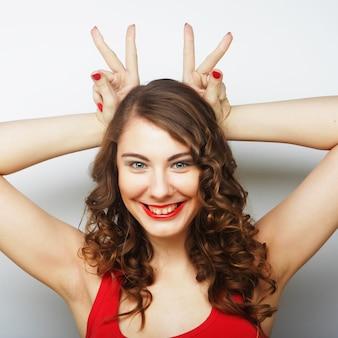 Donna divertente che fa il segno della mano. colpo dello studio.