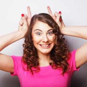 Donna divertente che fa il segno della mano