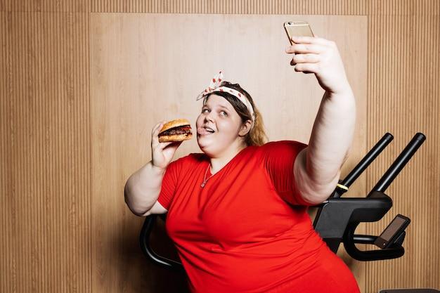 Una donna divertente vestita con abiti sportivi e con una benda sulla testa sta facendo selfie in piedi con un hamburger in mano accanto al tapis roulant