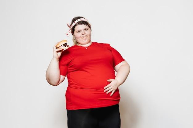 Una donna divertente vestita con abiti sportivi e con una benda sulla testa è in piedi con un hamburger in mano contro un muro bianco