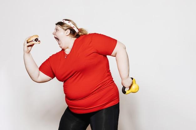 Una donna divertente vestita con abiti sportivi e con una benda sulla testa è in piedi con un hamburger in una mano e il peso nell'altra contro un muro bianco