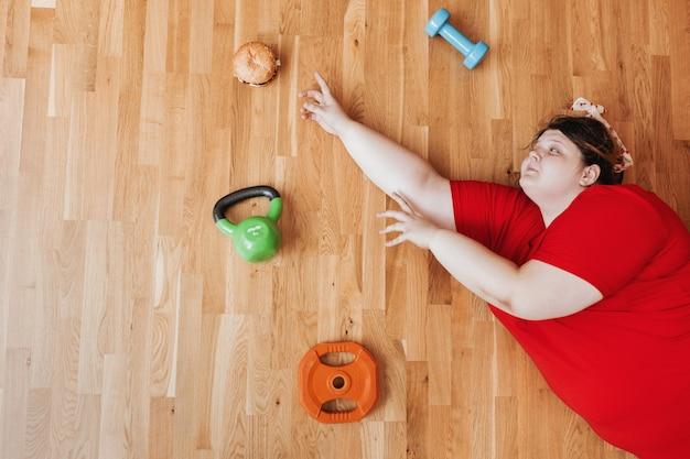 Una donna divertente vestita con abiti sportivi e con una benda sulla testa si trova sul pavimento accanto all'attrezzatura sportiva e tira le mani verso l'hamburger