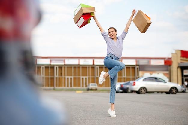 La donna divertente salta con i sacchetti di cartone sul parcheggio del supermercato. clienti felici che trasportano acquisti dal centro commerciale, veicoli