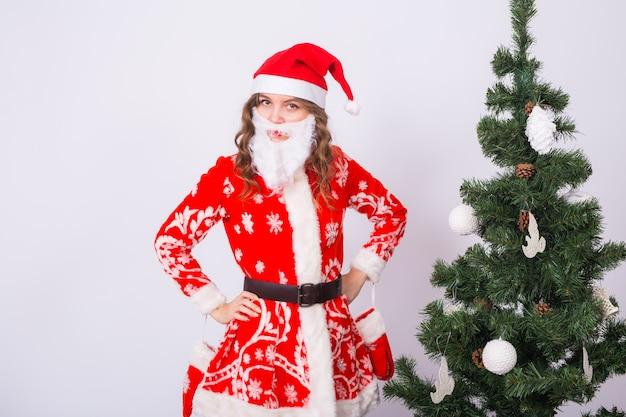 Donna divertente nell'indossare il costume di babbo natale sopra l'albero di natale
