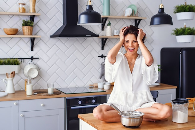 Una donna divertente con i capelli arricciati vestita in accappatoio bianco sente il panico in cucina durante la cottura.