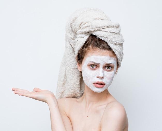 Donna divertente con un asciugamano sulla testa spalle nude maschera bianca sul viso.