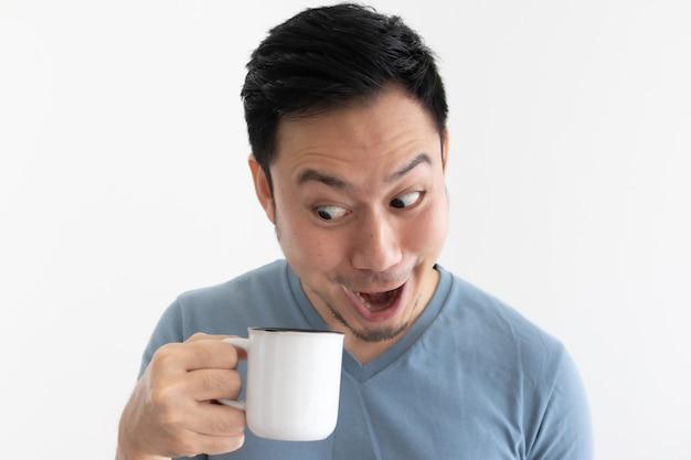 La faccia divertente di wow dell'uomo asiatico in maglietta blu beve il caffè dalla tazza bianca.
