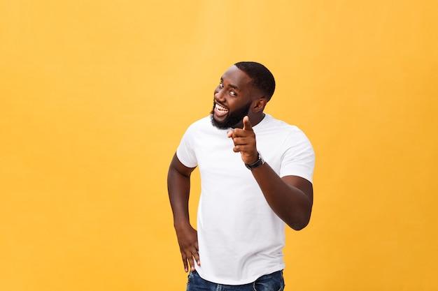 Divertente giovane cliente africano sorridente felicemente e puntando il dito indice verso la telecamera