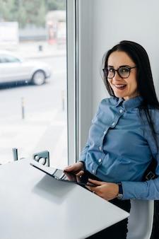 Divertente giovane ragazza dai capelli neri in camicia blu e occhiali in possesso di un tablet