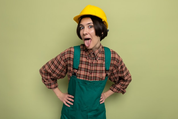 Divertente giovane donna costruttore in uniforme da costruzione e casco di sicurezza che sporge la lingua in piedi sul verde