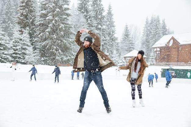 Divertente giovane coppia pattinaggio sul ghiaccio all'aperto