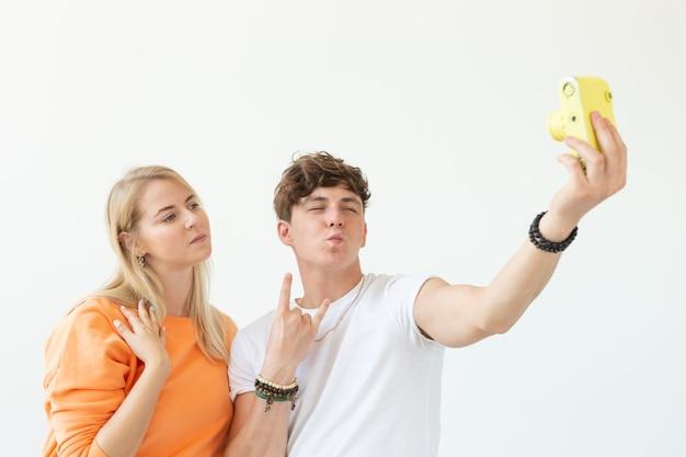 Giovani coppie divertenti nell'uomo sveglio di amore e donna affascinante che fa selfie sulla macchina fotografica di pellicola gialla dell'annata che posa su una priorità bassa bianca.