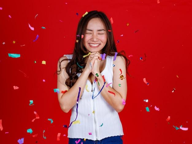 Divertente giovane e curata ragazza asiatica si sente eccitata e allegra mentre gioca con i coriandoli volanti dalla posizione sopra. studio girato su uno sfondo rosso.