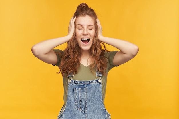 Divertente giovane donna allo zenzero indossa una tuta di jeans blu, tiene gli occhi chiusi, la bocca ampiamente aperta e si copre le orecchie con i palmi. isolato su muro giallo