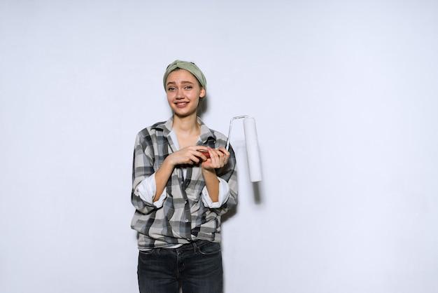 Divertente giovane pittrice dipinge le pareti di bianco con un rullo