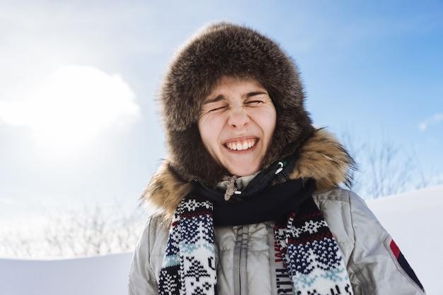 Una ragazza divertente con un caldo cappello di pelliccia sta viaggiando in islanda, fa molto freddo