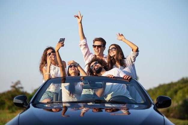 Divertenti ragazze e ragazzi con gli occhiali da sole sono seduti in una cabriolet nera sulla strada alzando le mani e facendo selfie in una giornata di sole. .
