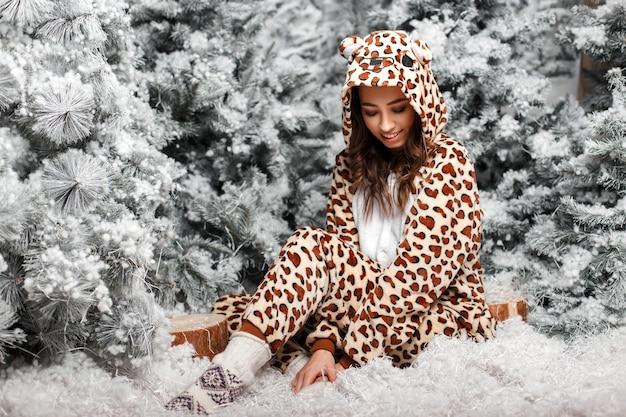 Divertente giovane donna felice in orso alla moda indossando pigiami con cappuccio seduto vicino ad alberi di natale con la neve in studio