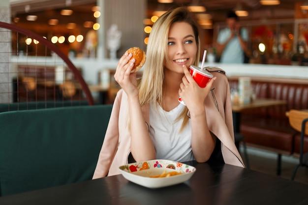Divertente giovane donna felice con un hamburger e cola mangiare fast food in un caffè