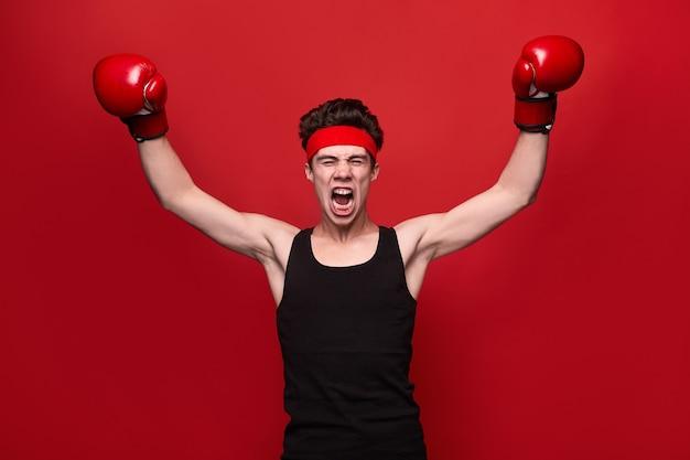 Divertente giovane in guantoni da boxe che alza le braccia e urla dopo la vittoria nella lotta contro lo sfondo rosso