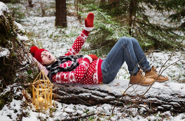 Giovane divertente in cappello rosso nella foresta di inverno