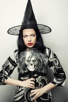 Divertente giovane donna vestita come strega con teschio