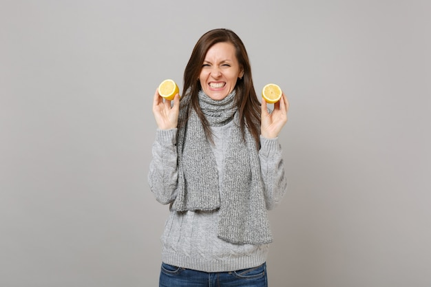 Divertente giovane donna in maglione grigio, sciarpa che tiene i limoni isolati su sfondo grigio muro, ritratto in studio. stile di vita sano, persone sincere emozioni, concetto di stagione fredda. mock up copia spazio.