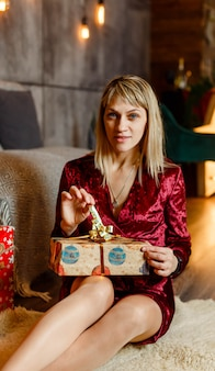 Giovane donna divertente che apre un presente. la femmina allegra apre un magico regalo di natale. donna felice con un regalo magico vicino all'albero di natale a casa. ragazza sorridente in vestito rosso con scatole regalo. felice anno nuovo