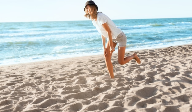 Giovane donna divertente sulla spiaggia al tramonto. bella femmina felice sulla riva del mare blu, stato d'animo positivo, vacanze estive, soleggiata, divertendosi concetto