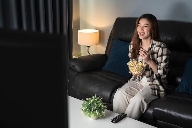 Divertente giovane donna che guarda la tv e mangia popcorn sul divano di notte