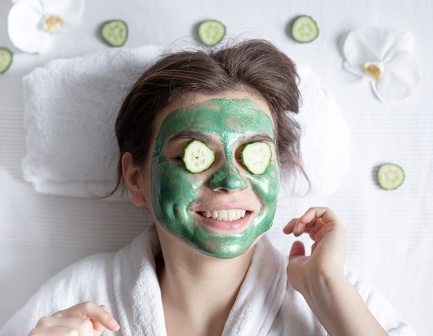 Divertente giovane donna con una maschera cosmetica sul viso e cetrioli sugli occhi.