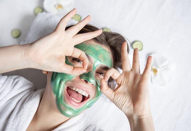 La giovane donna divertente con una maschera cosmetica verde sul viso sta riposando mentre giace nel salone della spa, vista dall'alto.