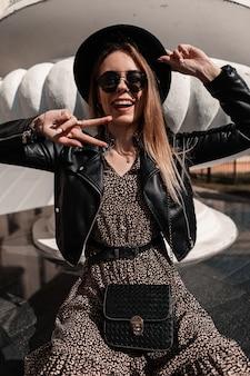 Una giovane donna divertente con occhiali da sole e cappello vintage in abito alla moda con giacca di pelle e borsa nera mostra un segno di pace e si siede in città