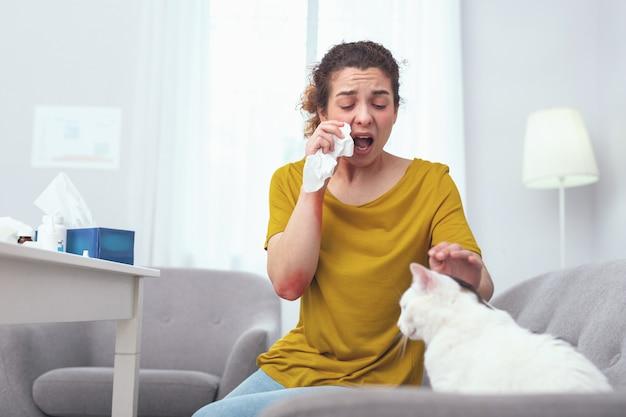 Problemi di pelliccia. giovane casalinga malata che utilizza gocce nasali mentre soffre di allergia al pelo di gatto