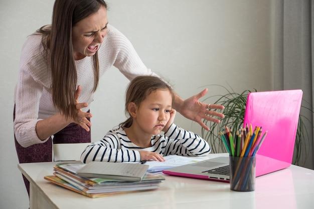 Donna adulta furiosa che grida alla figlia mentre aiuta a fare il suo compito a casa