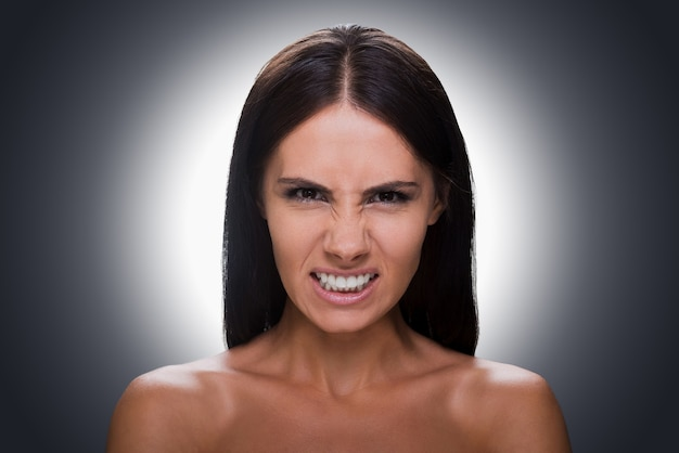 Bellezza furiosa. ritratto di una giovane donna furiosa a torso nudo che guarda la telecamera e fa una smorfia mentre si trova su uno sfondo grigio