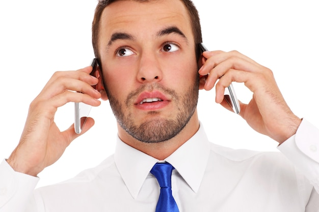 Un uomo d'affari furioso che parla contemporaneamente su due telefoni su sfondo bianco