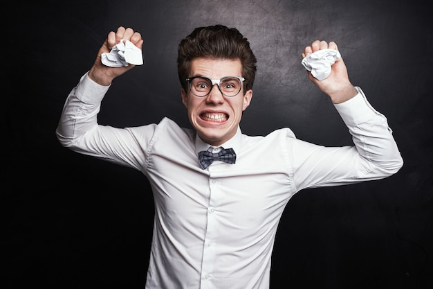 Uomo nerd furioso che accartoccia le carte
