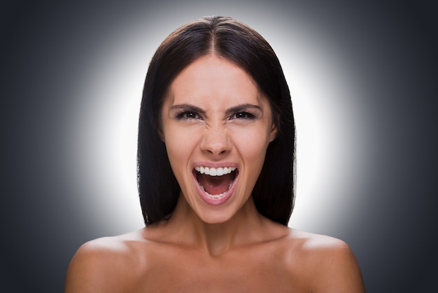 Donna furiosa. ritratto di giovane donna arrabbiata senza camicia che guarda la macchina fotografica e tiene la bocca aperta mentre si trova su uno sfondo grigio