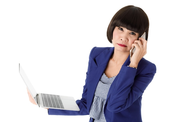 Furiosa giovane donna asiatica impiegata d'ufficio in abito blu che tiene il laptop aperto e chiama con il telefono cellulare su sfondo bianco