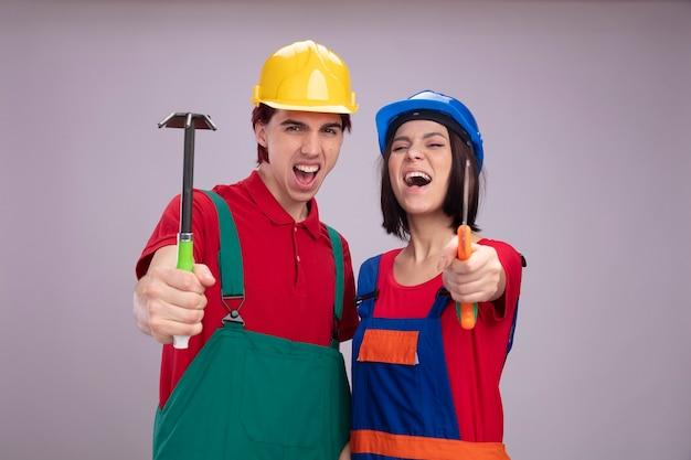 Giovani coppie furiose in uniforme del muratore e ragazzo del casco di sicurezza che allunga fuori hoerake ragazza che allunga la mano