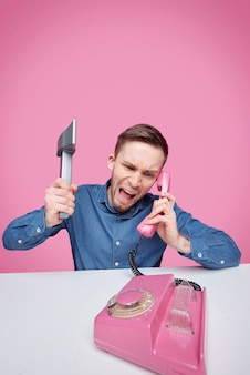 Giovane furioso con l'ascia che esprime rabbia mentre grida nel ricevitore del telefono di plastica rosa e si lamenta di qualcosa