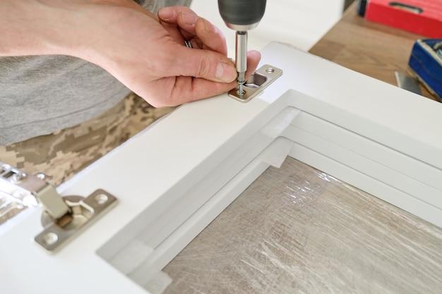 Assemblaggio di mobili. primo piano della mano dei lavoratori con strumenti professionali e dettagli di mobili