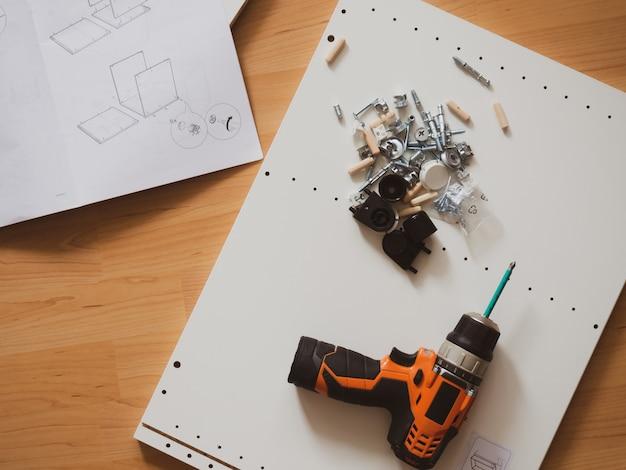 Concetto di montaggio dei mobili, accessori, cacciavite e istruzioni di montaggio con spazio per il testo