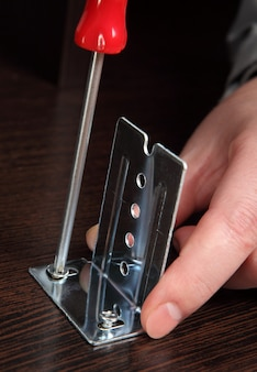 Montaggio di mobili, staffe di installazione guide di scorrimento con un cacciavite a mano.