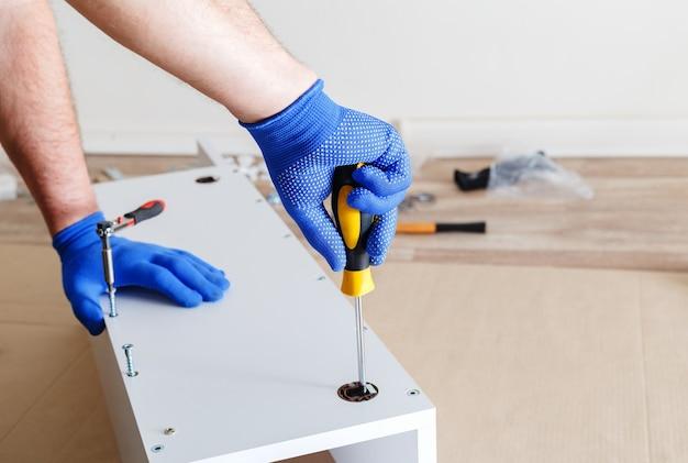 Montaggio mobili. mani maschili in guanti blu master raccoglie mobili utilizzando strumenti cacciavite, strumento a casa. traslochi, ristrutturazioni, riparazioni e ristrutturazioni di mobili.